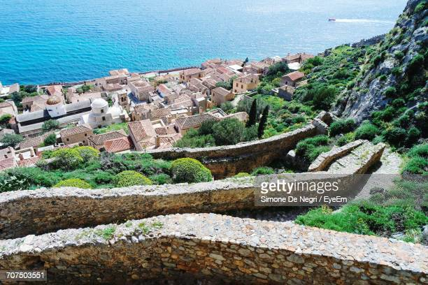 high angle view of buildings by sea at monemvasia - peloponnese stock photos and pictures