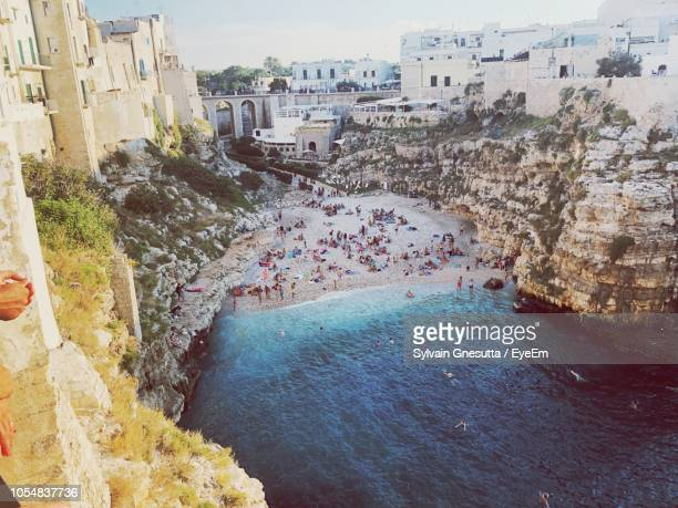 high angle view of buildings by sea - polignano a mare stock photos and pictures