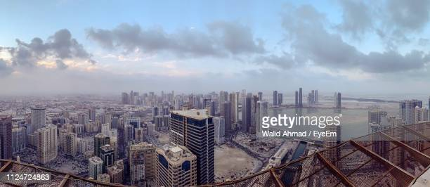 high angle view of buildings in city against sky - emirate of sharjah stock pictures, royalty-free photos & images
