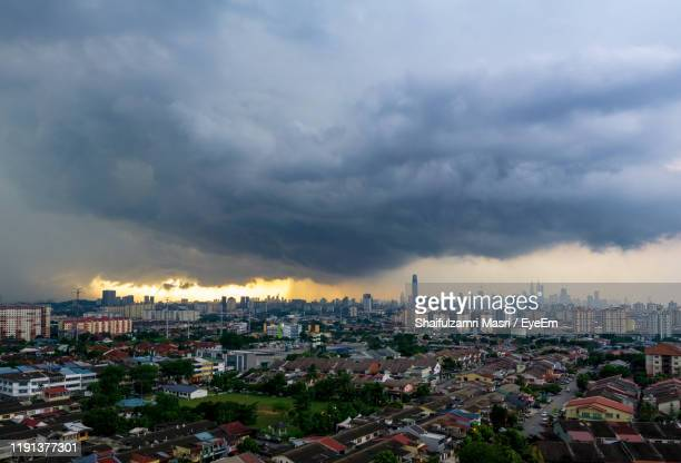 high angle view of buildings in city against storm clouds - shaifulzamri - fotografias e filmes do acervo