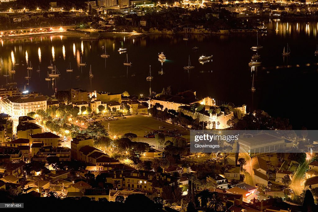 High angle view of buildings lit up at night near a harbor, Nice, France : Foto de stock