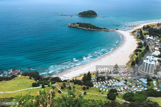 high angle view of buildings on beach - bay of plenty stock pictures, royalty-free photos & images