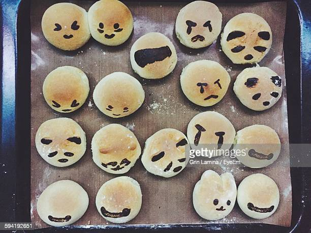 High Angle View Of Buns With Various Smiley Faces In Tray
