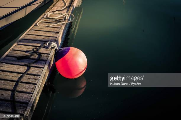 high angle view of buoy hanging on pier over lake - buoy stock photos and pictures