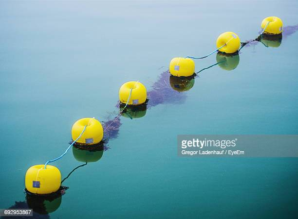 high angle view of buoys on sea - buoy stock photos and pictures