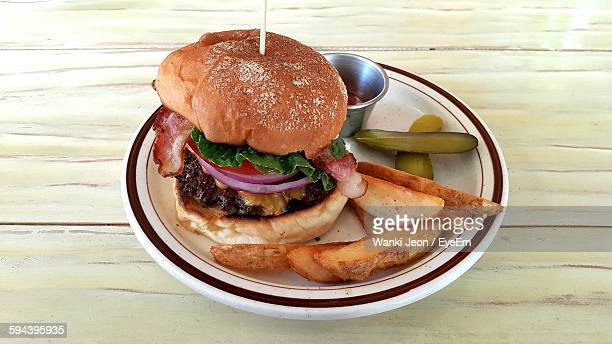 High Angle View Of Burger By Potato Wedges In Plate On Wooden Table