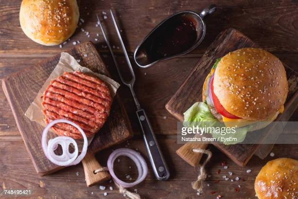 High Angle View Of Burger With Cutlet And Onion Slices On Wooden Table