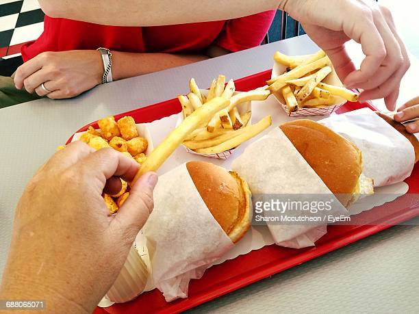 high angle view of burger with french fries on table - fast food french fries stock pictures, royalty-free photos & images