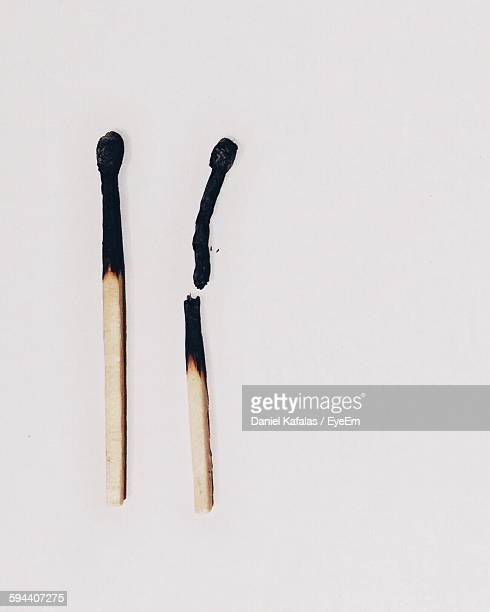 high angle view of burnt matchsticks against white background - fiammifero foto e immagini stock