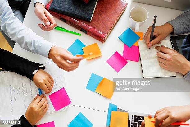 High angle view of business people analyzing notes at table