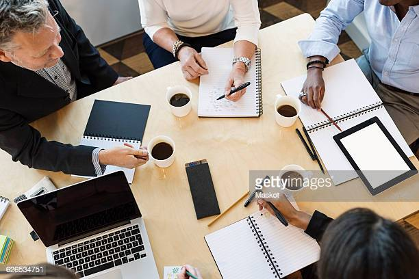 High angle view of business people discussing on table in office