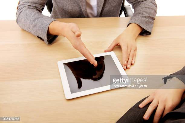 High Angle View Of Business People Discussing Over Digital Tablet On Desk At Office
