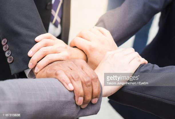 high angle view of business people forming hand chain on footpath - four people stock pictures, royalty-free photos & images