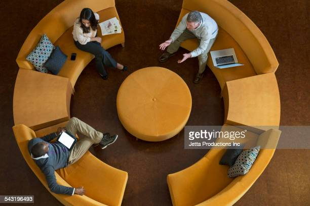 High angle view of business people talking on circular sofa