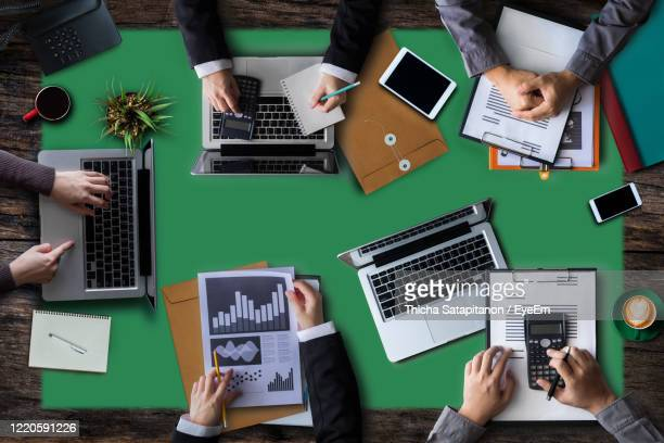 high angle view of business people working at desk - business plan stock pictures, royalty-free photos & images