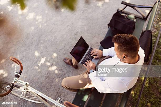 High angle view of businessman using laptop while sitting on park bench