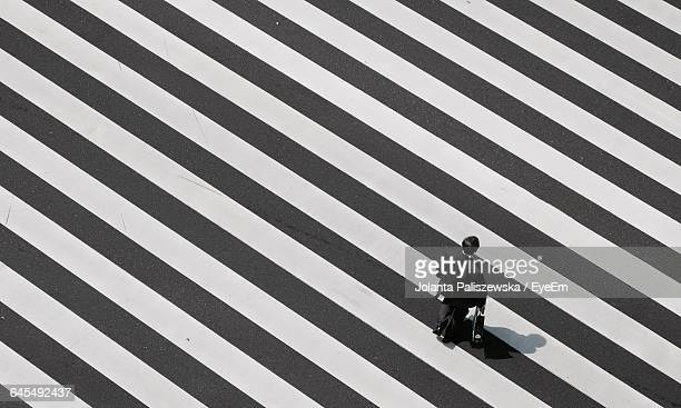 high angle view of businessman walking on crosswalk - zebra crossing stock pictures, royalty-free photos & images