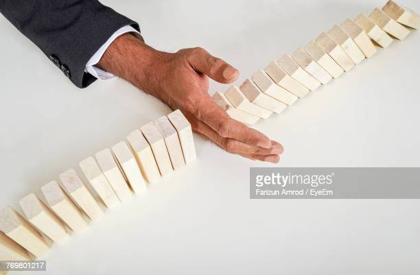High Angle View Of Businessman With Toy Blocks On White Table