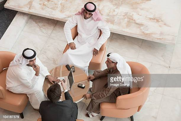 high angle view of businessmen having a meeting - oriente medio fotografías e imágenes de stock
