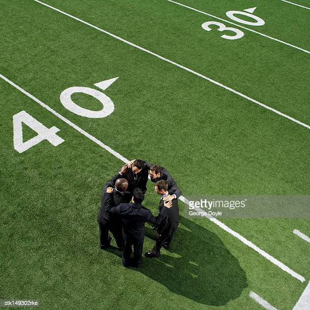 high angle view of businessmen in a huddle on a football field - forty yard line stock pictures, royalty-free photos & images