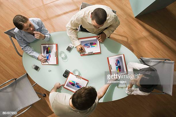High angle view of businesspeople in meeting with pie charts