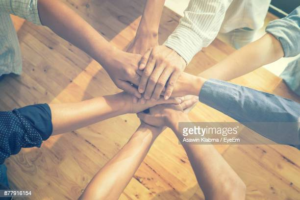 High Angle View Of Businesspeople Stacking Hands Over Table