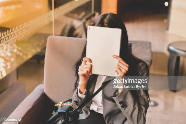 high angle view of businesswoman covering face with digital tablet in office - verlegen stockfoto's en -beelden