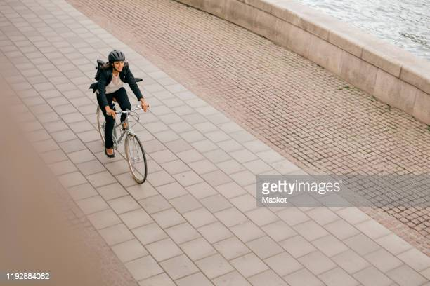 high angle view of businesswoman riding bicycle on footpath - cycling stock pictures, royalty-free photos & images