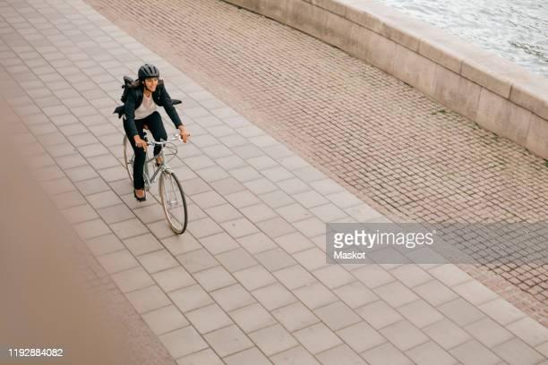 high angle view of businesswoman riding bicycle on footpath - radfahren stock-fotos und bilder