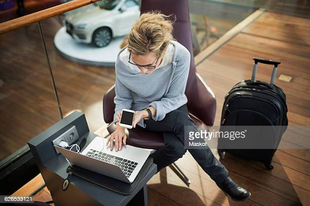 High angle view of businesswoman using laptop and smart phone at airport lobby