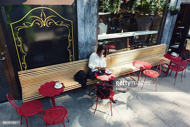 High angle view of businesswoman using smart phone at sidewalk cafe