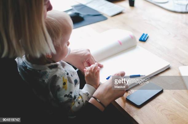 High angle view of businesswoman with baby girl writing in diary at table in creative office