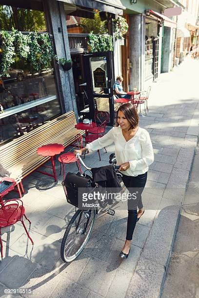 High angle view of businesswoman with bicycle walking on sidewalk