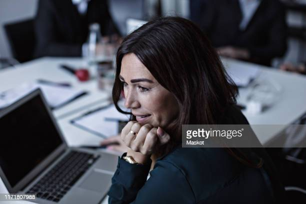 high angle view of businesswoman with hand on chin looking while sitting at conference table in board room - formal businesswear stock pictures, royalty-free photos & images