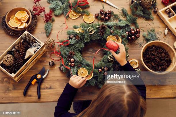 high angle view of busy woman standing at desk and using decorative ribbon while making christmas wreath - preparation stock pictures, royalty-free photos & images