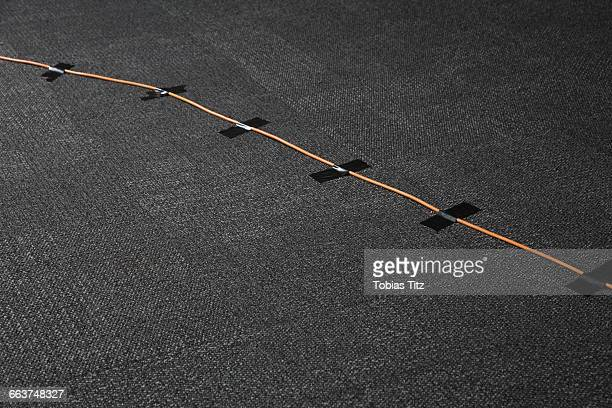 High angle view of cables attached on black carpet