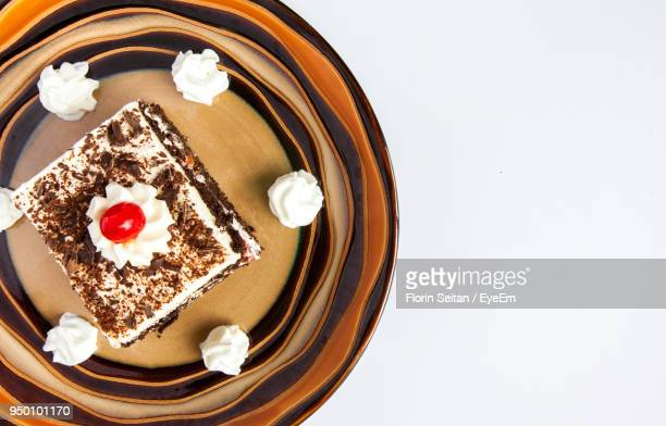 high angle view of cake in plate over white background - florin seitan stock pictures, royalty-free photos & images