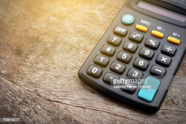 High Angle View Of Calculator On Wooden Table