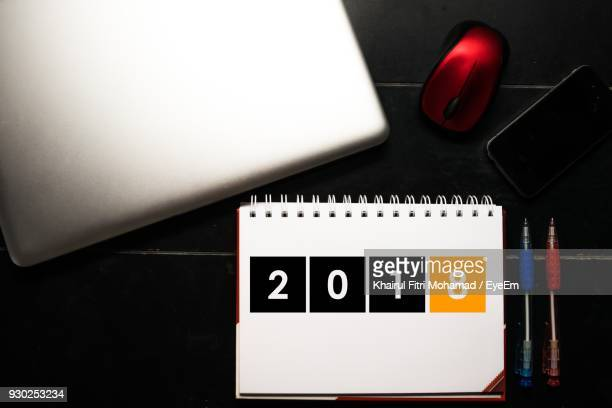 High Angle View Of Calendar With Pens And Technology On Table