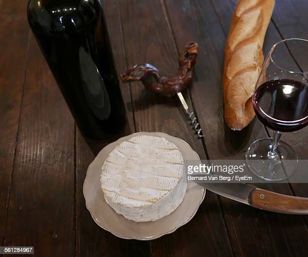high angle view of camembert and baguette with wine on wooden table - camembert stock photos and pictures