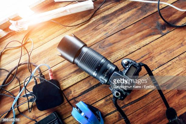 high angle view of camera on wooden table - photographic equipment stock pictures, royalty-free photos & images