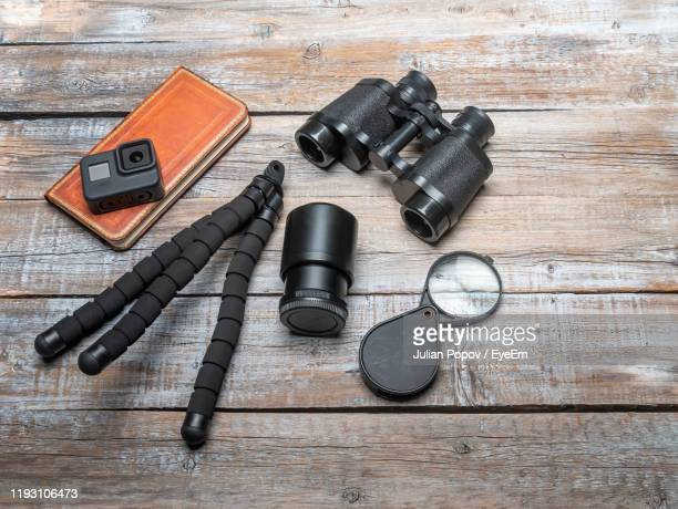 high angle view of camera with binoculars and book on table - 三脚 ストックフォトと画像