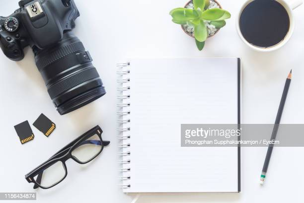 high angle view of camera with coffee and plant on white background - medium group of objects stock pictures, royalty-free photos & images
