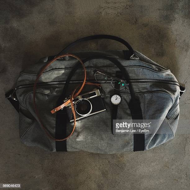 High Angle View Of Camera With Eyeglasses And Wristwatch On Bag