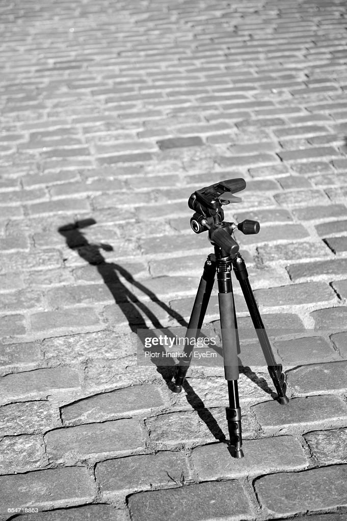 High Angle View Of Camera With Tripod On Footpath During Sunny Day : Stock Photo