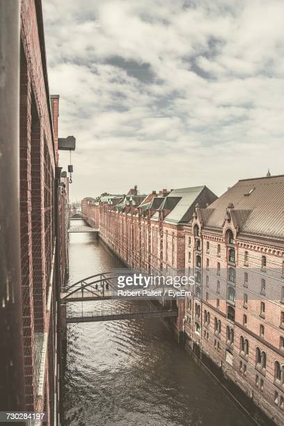 High Angle View Of Canal Amidst Buildings At Speicherstadt In City