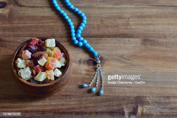 High Angle View Of Candies And Necklace On Wooden Table