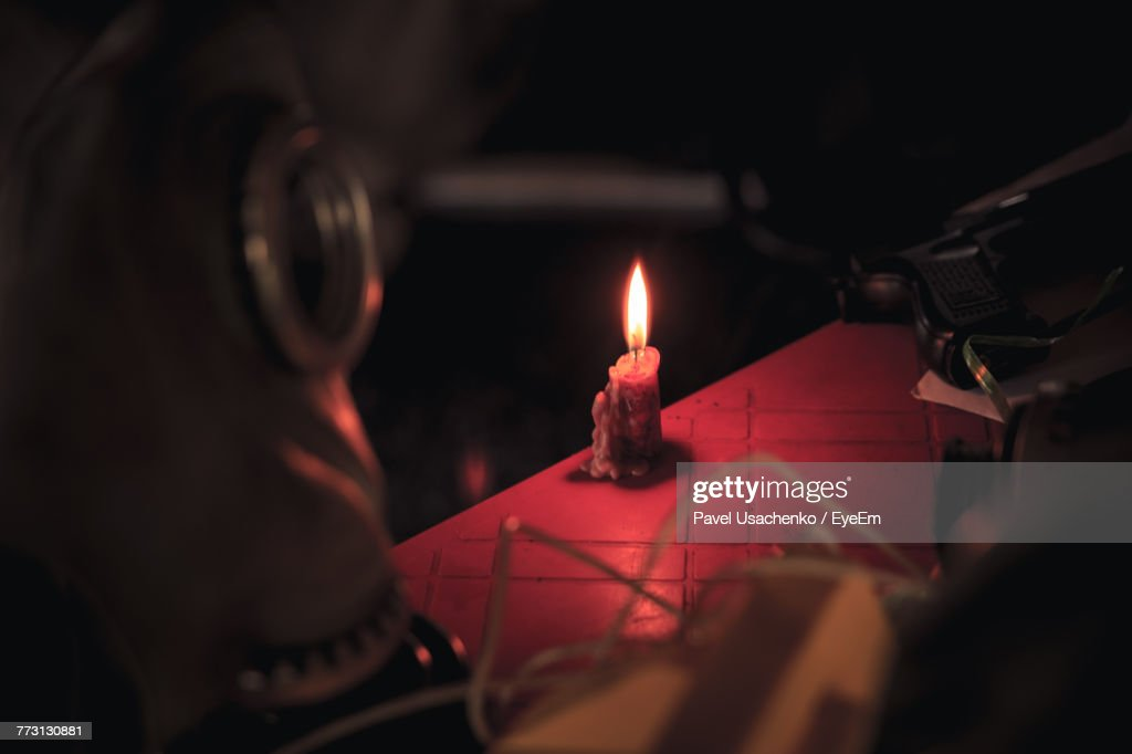 High Angle View Of Candle Burning On Table In Darkroom : Photo