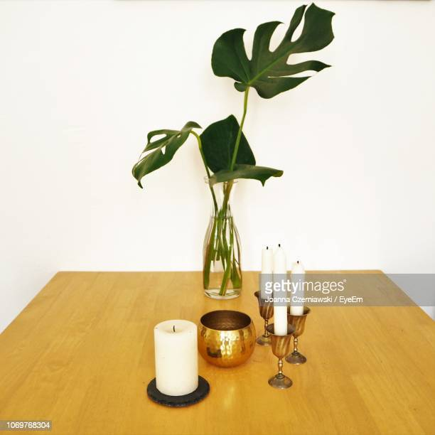 high angle view of candles and vase on table by wall - candlestick holder stock pictures, royalty-free photos & images