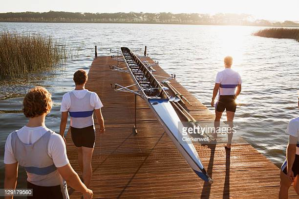 erhöhte ansicht von einer kanu und menschen am pier - mannschaftssport stock-fotos und bilder